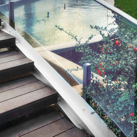 Decorative Small Pedestrian Bridge With Stainless Steel Railing And Wooden Stairs In Tropical Garden Or Park.