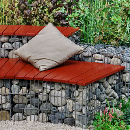 Designed Backyard Garden Patio and Outdoor Party Place. Modern Garden Design and Landscaping. Round Bench Made from Gabions with Wooden Seat. Landscaped Family Resting Area with Fireplace. 版權商用圖片