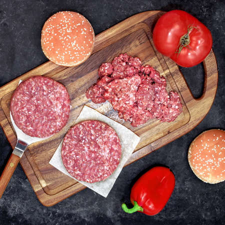 Ingredients For Cooking Steak Burgers or Cheeseburger, Overhead View. Raw Ground Beef Meat Cutlets or Patties on Wooden Chopping Board. Homemade Cooking Food For Family Party, Top View.