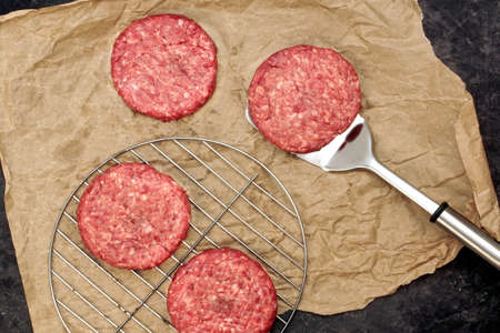 Ground Beef Patties for Grilling and Roasting. Raw Minced Steak Burgers from Beef Meat on Black Background. BBQ Grill Tools with Raw Beef Hamburger Patties. Burger Cutlets On Paper And Grill Grate. 版權商用圖片