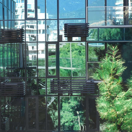 Office Building With Glass Mirror Facade. Curtains Wall Of Apartments House With Glazing Facade. Background With Park Reflection And Town In Windows. Ac Box Or Basket On The Facade. Eco Design View.