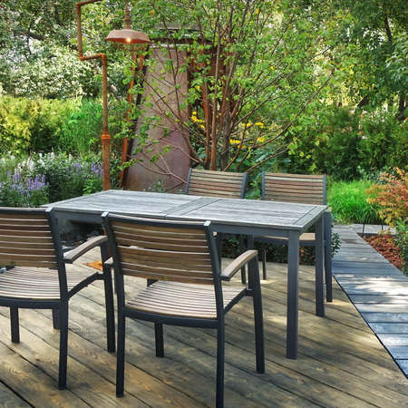 Garden Wooden Patio with Wooden Dinning Table and Chairs on Harwood Decking Floor. Wooden Terrace in Garden with Outdoor Furniture. Landscaped Backyard.