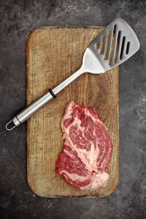 Raw Marbled Loin Beef Steaks and Grill Tools On Wooden Cutting Board. Beef Steaks On Spatula Ready for BBQ or Grilling, Overhead View. Raw Striploin Marbled Beef Steaks on Black Background, Top View. 版權商用圖片