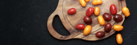 Plum Cherry On White Round Cutting Board. Assorted Plump Cherry Tomatoes On Wooden Cutting Board. Scattered Red, Yellow And Black Plum Cherry Tomato On Black Grunge Background.