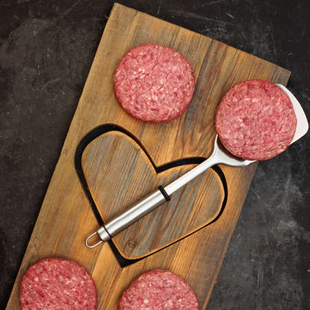 Patty of Minced Meat On Wooden Board with Shape of Heart. Raw Beef Steak Burgers on Wood Board with Heart Shape. Raw Steak Burgers Cutlets And BBQ Grill Tools Overhead View. Ground Beef Burgers.