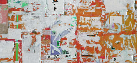 Scratched Advertising On Grunge Wall Panoramic Rough Background. Exposed Weathered Urban Wall with Torn Street Posters, Paper and Stickers. Vintage Billboard With Torn Poster, Paper, Ads Wide Grunge Background Or Texture. 版權商用圖片