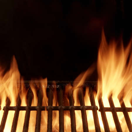 Barbecue Fire Grill Isolated On Black Background. BBQ Flaming Grill Background Isolated. Hot Barbeque Charcoal Cast Iron Grill With Bright Flames. Stock Photo
