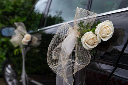 Wedding black car decorated with white roses