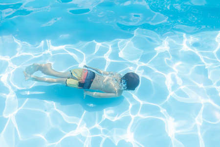 Kid diving in a swimming pool in summer Stock Photo