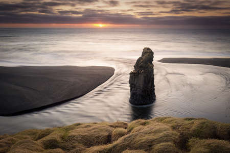 Dyrholaey lighthouse over black sand beach in Iceland
