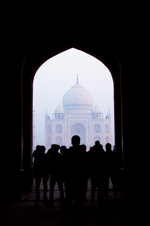 visitors: Taj Mahal and its visitors framed by a entrance gate. Stock Photo