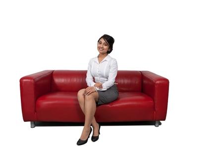 Attractive Asian businesswoman sitting on sofa