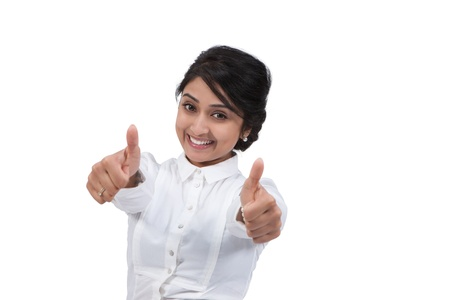 Happy Asian businesswoman gesturing thumbs up against white background photo