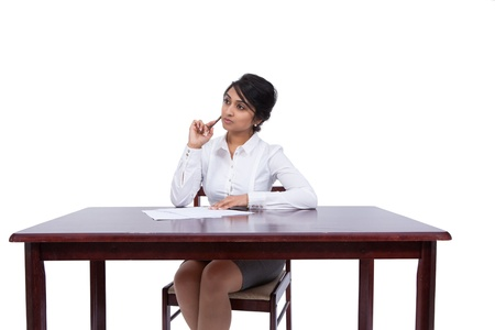 Attractive Asian businesswoman thinking at her desk