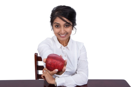 Attractive young businesswoman offering an apple photo