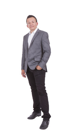 Portrait of a handsome young businessman posing with hands in pocket against white