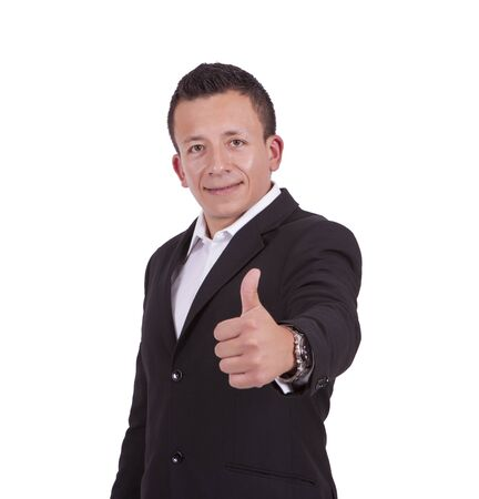 Portrait of a smiling young businessman gesturing thumbs up while standing against white Banco de Imagens