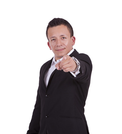 Portrait of a young businessman pointing towards camera while standing against white
