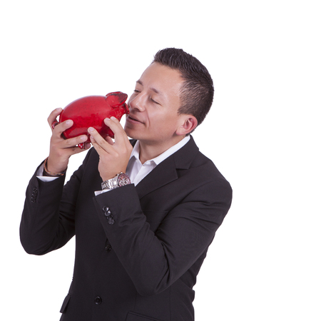 Image of a handsome young mixed race businessman kissing his piggy bank photo