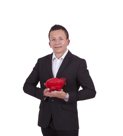 Image of a smiling young businessman posing with a piggy bank while standing against white photo