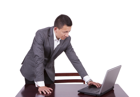 Young businessman standing and using laptop at work