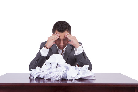 Image of a tensed young businessman with crumpled papers on his desk Banco de Imagens