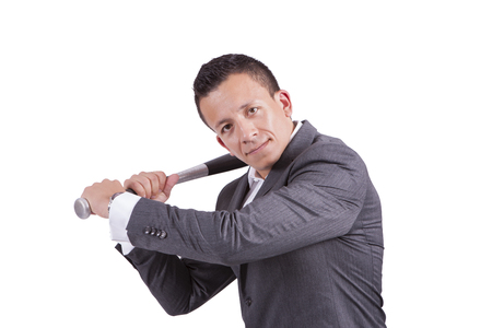 Portrait of a young businessman swinging his baseball bat while standing against white