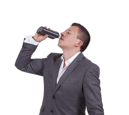 Image of a handsome young businessman drinking water while standing against white