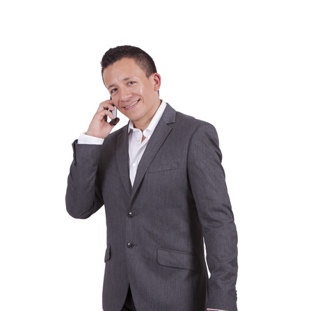 Image of a young businessman communicating over cell phone while standing against white Banco de Imagens