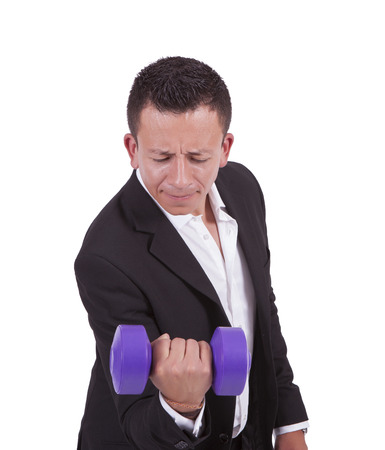 Image of a young businessman posing with dumbbell while standing against white