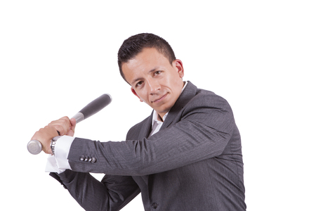 Portrait of a mixed race businessman swinging his baseball bat while standing against white