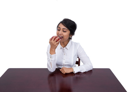 Attractive young businesswoman eating an apple photo