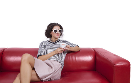 legs crossed at knee: Thoughtful young woman with a coffee cup sitting on a red couch against white background