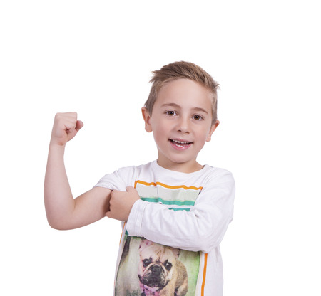 Image of a smiling elementary boy flexing his biceps against white Banco de Imagens