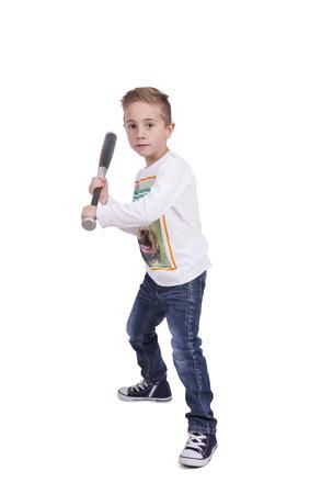 Portrait of a elementary boy swinging his baseball bat against white background Banco de Imagens
