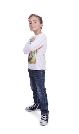 Portrait of a elementary boy with arms crossed standing against white background Banco de Imagens