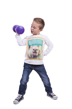 Image of a elementary boy exercising with dumbbell against white background