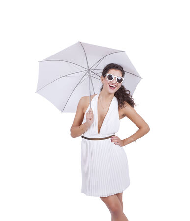Happy young woman wearing sunglasses and umbrella in hand posing against white background