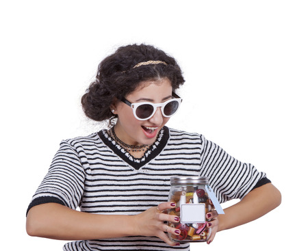Image of a excited young woman with a jar of candies Banco de Imagens
