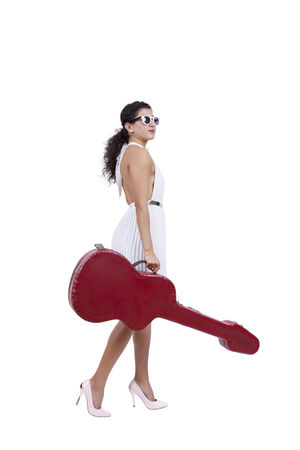Side view of an attractive young female posing with guitar case