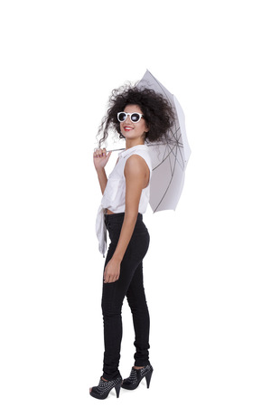 Side view of an attractive young woman posing with sunglasses and umbrella against white background Banco de Imagens