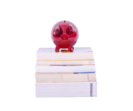 Red piggy bank on stack of books isolated on white background photo