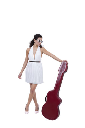 Attractive young female wearing sunglasses posing with guitar