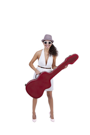 Happy young female wearing sunglasses posing with guitar photo