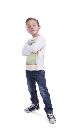 Cute elementary boy with arms crossed posing against white  Banco de Imagens