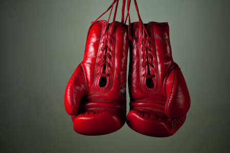 boxing glove: Boxing gloves hanging from laces on a grey background