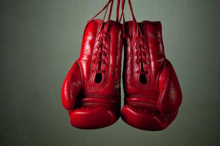 guantes de boxeo: Guantes de boxeo colgando de cordones sobre un fondo gris