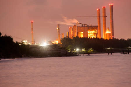 A smoking industrial power plant on seaside at night photo