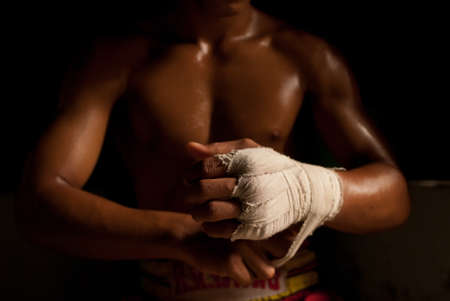 combative sport: The muscular fighter tying tape around his hand preparing to box