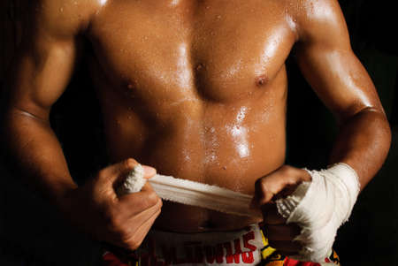 The muscular fighter tying tape around his hand preparing to fight Stock Photo